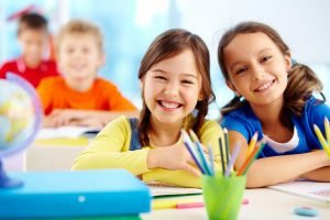 A pair of smiling students waiting in their classroom