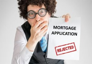 Disappointed man showing paper with denied mortgage application