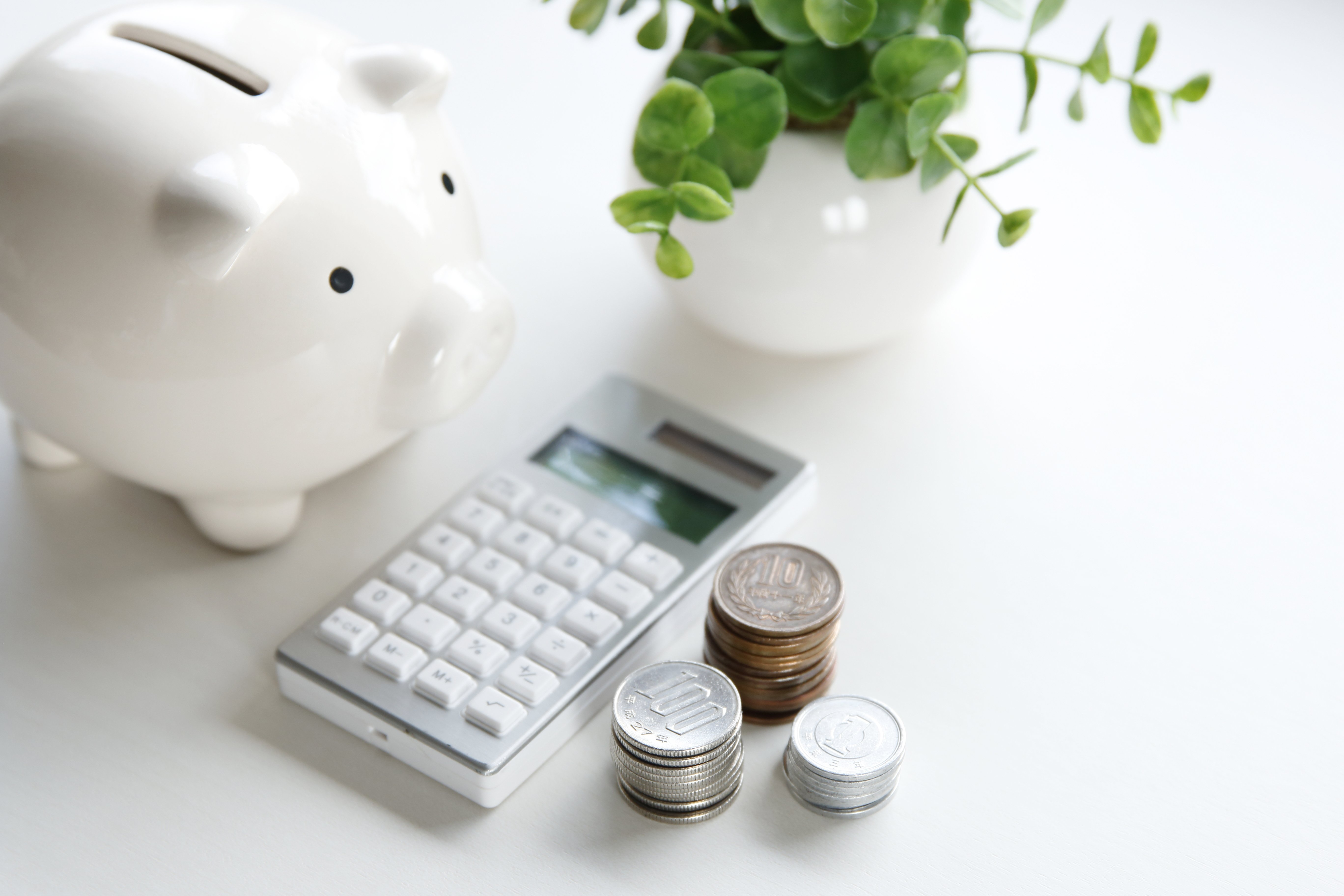 A white piggy bank, electronic calculator, and coins