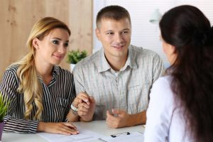 Couple discussing with real estate agent