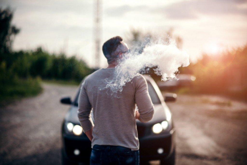Man blowing vapor from e-cigarette