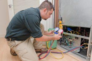HVAC technician charging a heat pump