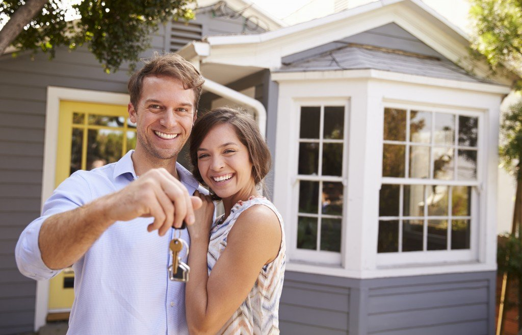 Couple with keys outside new home