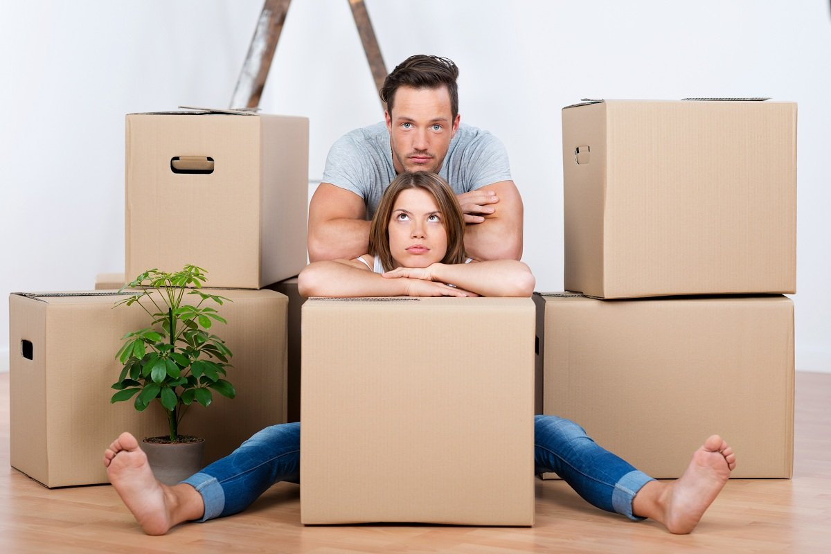 Couple Sitting Between Boxes