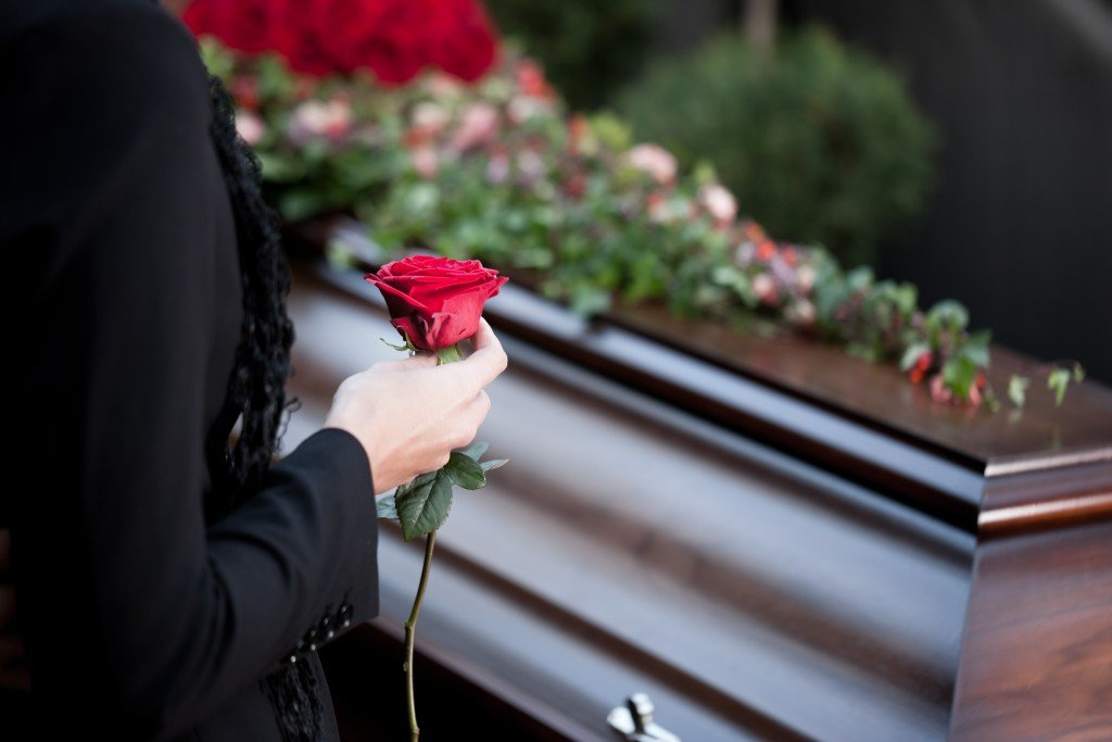 someone holding a rose next to a coffin