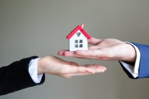 one person handing a small house to another person