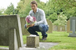 Man placing flowers near headstone