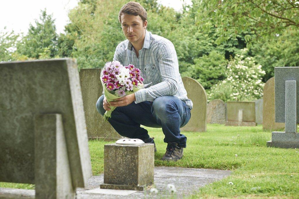 Man placing flowers near headstone