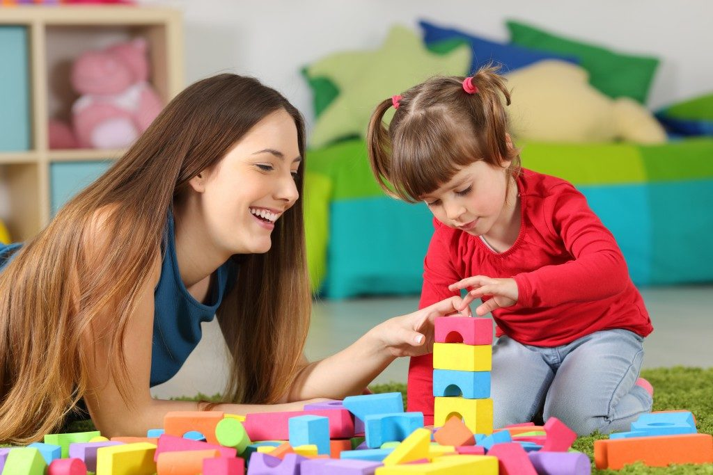 mother helping her child with toy blocks