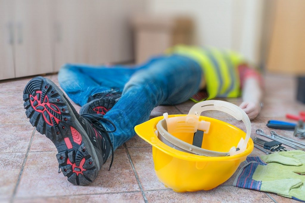 Man lying down on the floor after accident at work