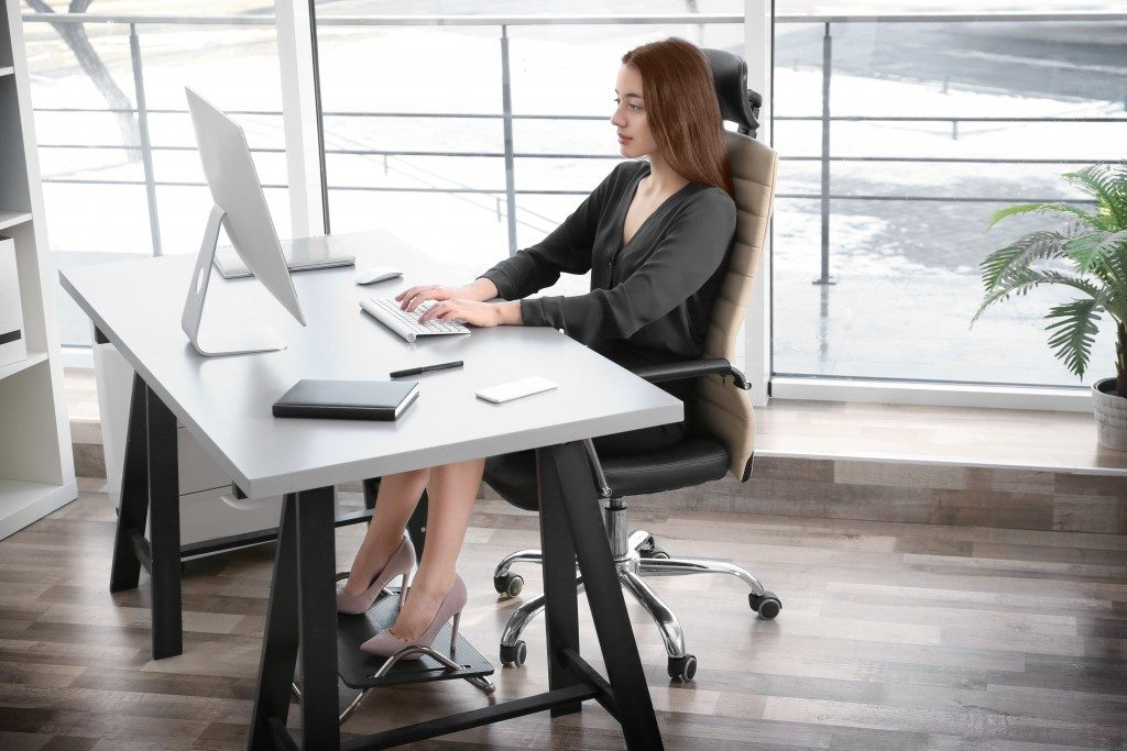 woman sitting in an ergonomical chair while working