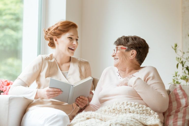 nurse reading to an elderly woman