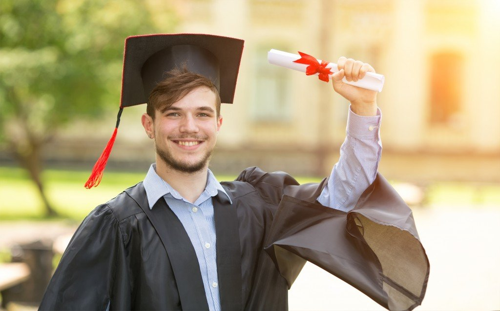 A fresh graduate holding up his diploma