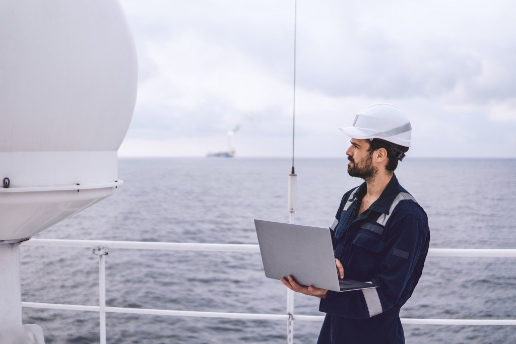 Man working on the boat with laptop