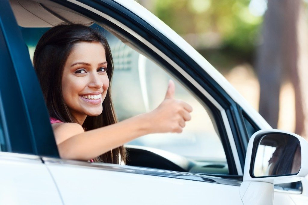 Woman driver with her thumb up